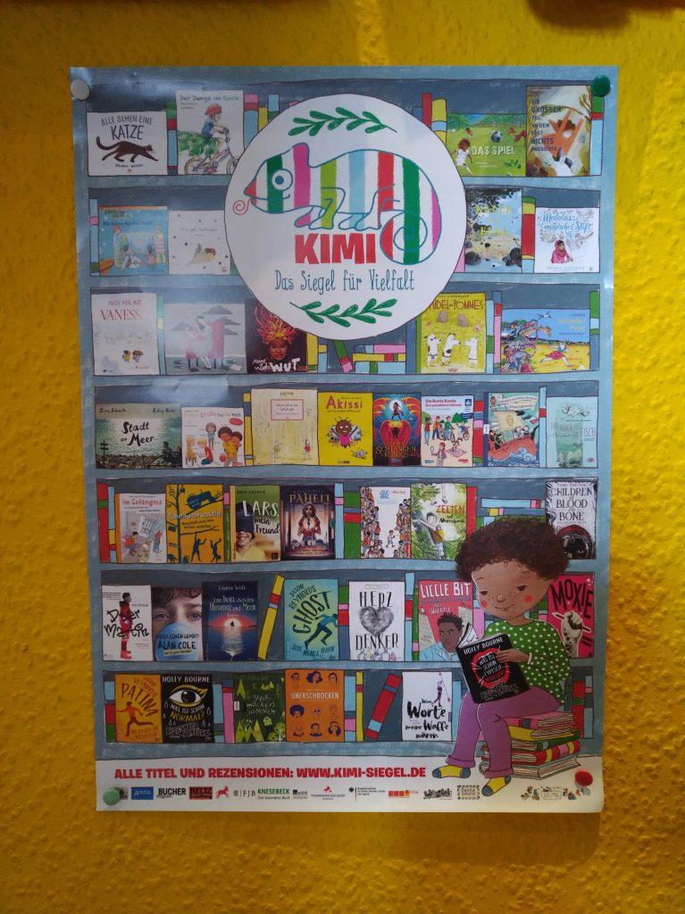 Poster der geehrten Bücher, auf denen die Cover abgebildet sind und ein lesendes Kind, das auf einem Bücherstapel sitzt.